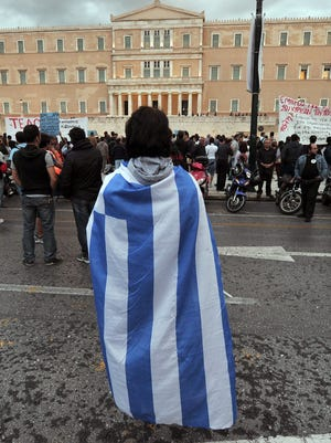 A Greek protester stands in front of the parliament in Athens on November 7, 2012