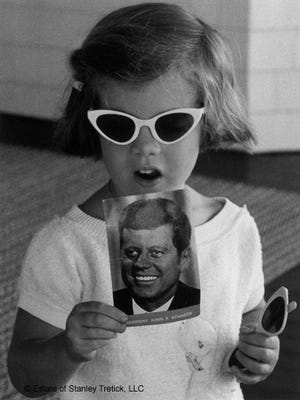 Young Caroline holds a postcard of her father, the President, in this shot by Stanley Tretick from Ketty Kelley's new book 'Capturing Camelot.'