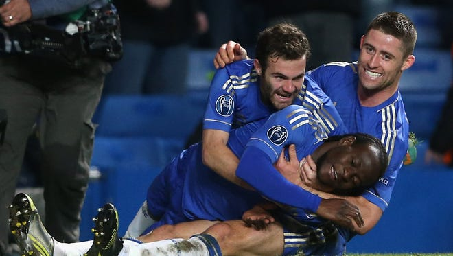 Victor Moses, bottom, celebrates with teammates Juan Mata, left, and Gary Cahill after scoring the winning goal in Chelsea's 3-2 Champions League win over Shakhtar Donetsk on Nov. 7.