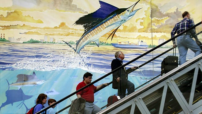 Travelers ride an escalator to the departure level of Terminal 1 at Fort Lauderdale-Hollywood International Airport in front of a mural by artist Guy Harvey.