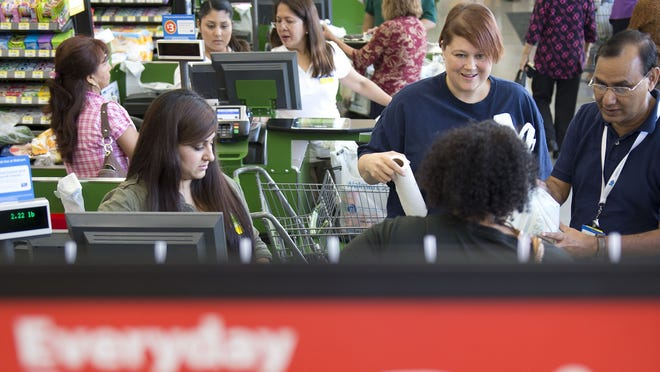 Cashiers ring up purchases on the opening day of a Walmart Neighborhood Market in Panorama City, Calif., in September.
