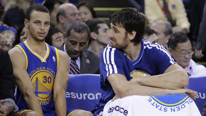 Golden State Warriors' Stephen Curry (30) and Andrew Bogut watch from the bench during the second half of an NBA basketball game against the Memphis Grizzlies Friday, Nov. 2, 2012, in Oakland, Calif. (AP Photo/Ben Margot) ORG XMIT: OAS113