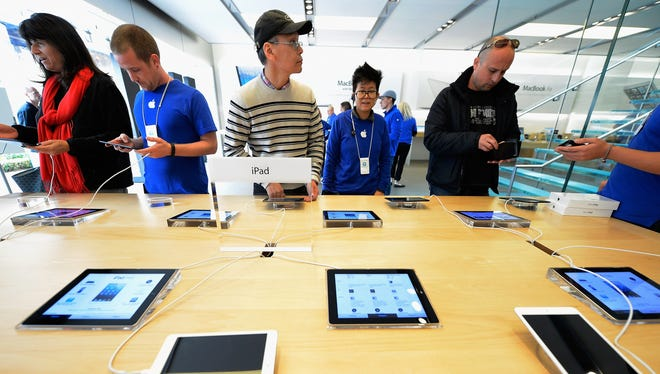 Customers try out new iPad minis at the Apple Store in Los Angeles, Nov. 2, 2012.