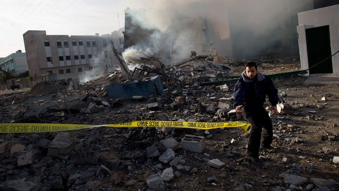 A Hamas officer secures the area after an Israeli airstrike in Gaza City.