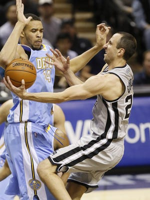 Spurs guard Manu Ginobili drives on Nuggets center JaVale McGee.