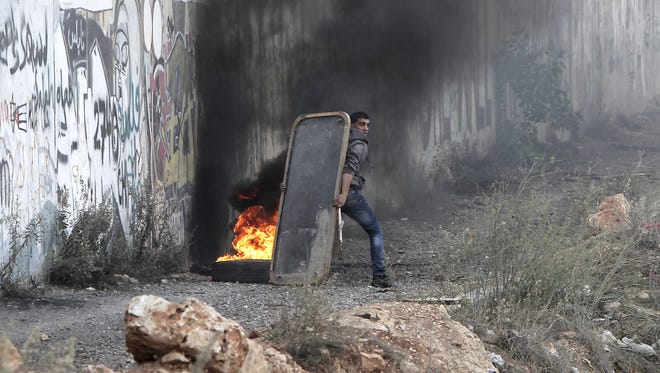 A Palestinian youth take cover Saturday behind a makeshift barrier during clashes with Israeli soldiers at the Qalandia checkpoint, in the Israeli occupied West Bank. Israel's brutal strikes on Gaza, while killing 12, have been viewed by some as a political bonanza for Hamas.