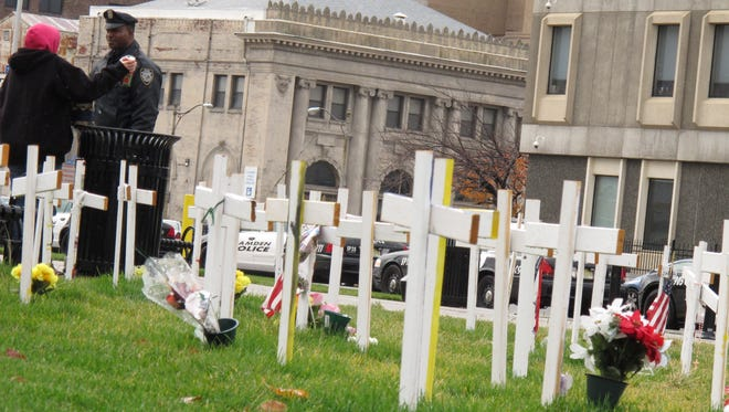 A woman and a Camden police officer speak near a display of crosses in Roosevelt Park in Camden, N.J. on Nov. 13. The crosses are symbols of the city's homicide victims.