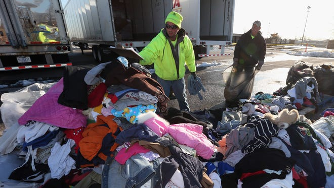 James Vouloukos, left, and William Ferris sort through donated clothes at Oceanside Park in the aftermath of Superstorm Sandy on Nov. 9 in Oceanside, N.Y.
