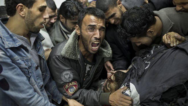 A Palestinian man cries next the body of a dead relative in the morgue of Shifa Hospital in Gaza City. Israeli has stepped up its air assault against Hamas militants in Gaza.