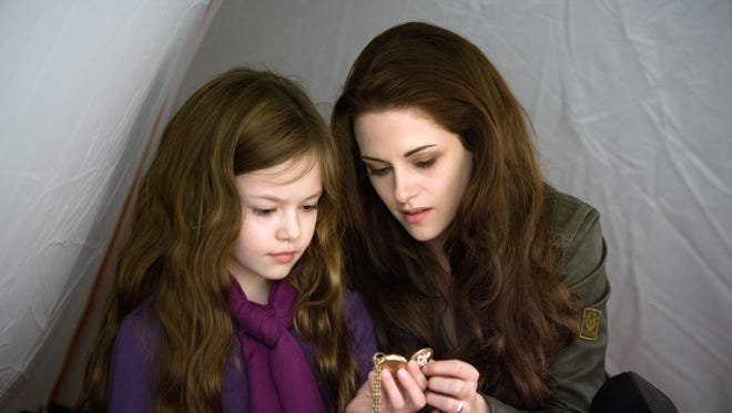 Mackenzie Foy, left, plays half-human, half-vampire child Renesmee, daughter of Bella (Kristen Stewart,, right), in 'The Twilight Saga: Breaking Dawn -- Part 2.'