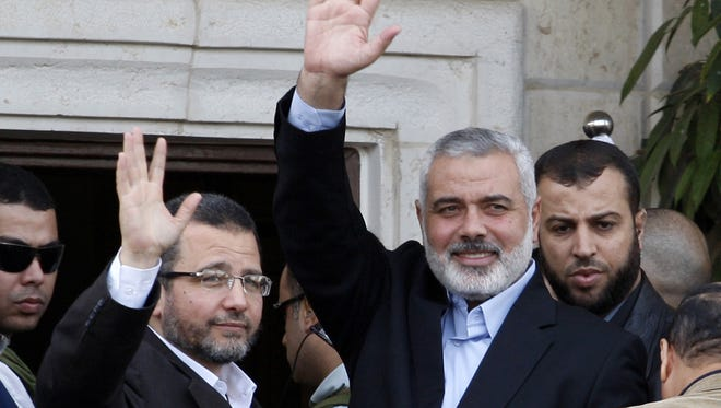 Hamas Prime Minister Ismail Haniyeh, right, and Egyptian Prime Minister Hesham Kandil wave to the crowd as they meet in Gaza City Friday.