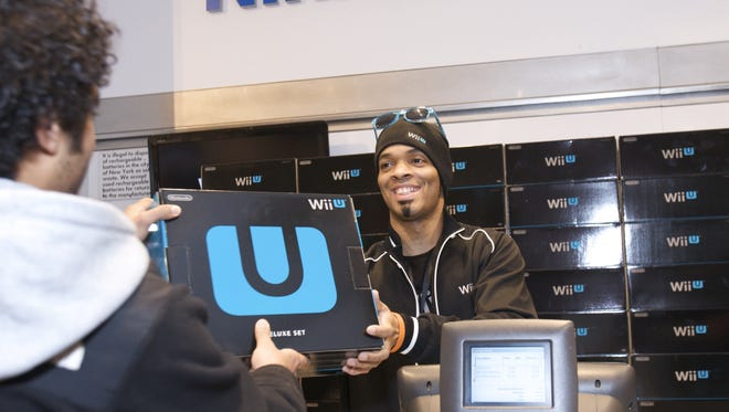 A customer buys one of the first Wii U systems at the midnight launch event at Nintendo World in New York.