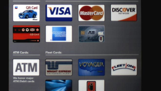 Credit card logos are displayed on a storefront window in Atlanta.
