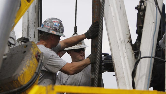 Crew members work on a drilling platform on a Weld County farm near Mead, Colo., in the northeastern part of the state.