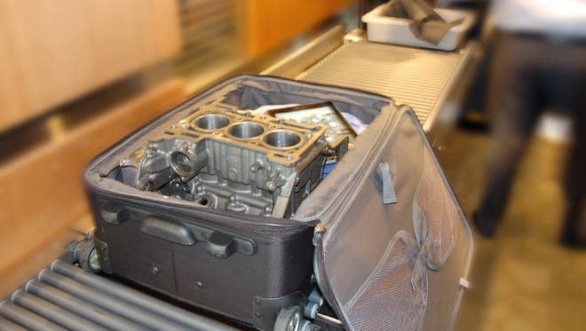 In a gag, Ford shows off how the block of its smallest engine will fit in a suitcase