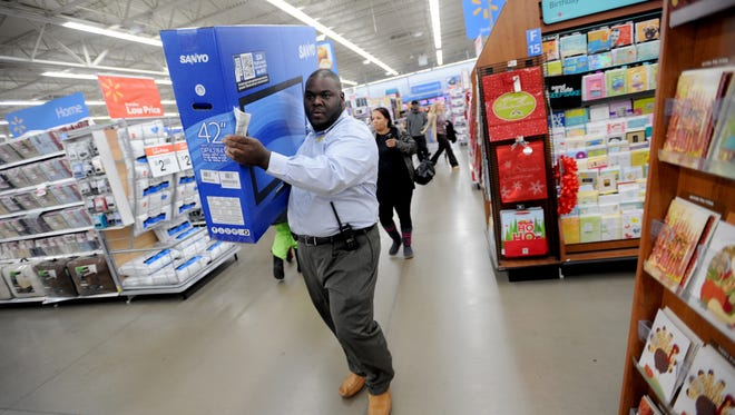 Store manager Keith Richards carries a Sanyo 42-inch LCD HDTV to the customer service counter to put it on layaway for a shopper at a Walmart store in the Chatham neighborhood on the South Side of Chicago.