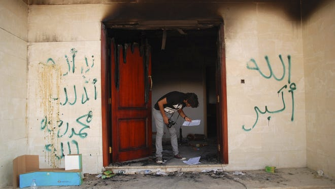 Amid the wrecked U.S. Consulate in Benghazi, Libya, a man examines documents on the day after the Sept. 11 attack that killed Ambassador Christopher Stevens and three other Americans.