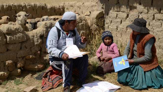A census enumerator asks questions to an aymara family at the Wichi Wichi community, 40 Km from La Paz in the Bolivian high plateau, during a national census day on Wednesday.