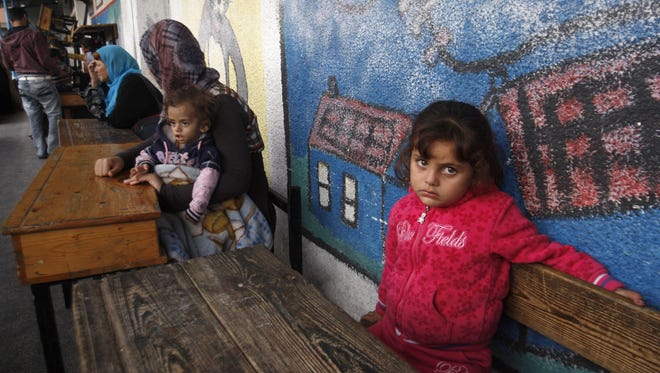 Palestinians sit inside a United Nations-run school in Gaza City on Wednesday before the implementation of a cease-fire. About 10,000 Gazans have sought shelter in U.N.-run schools after the Israeli military dropped leaflets on the territory calling on residents of certain areas to evacuate their homes.