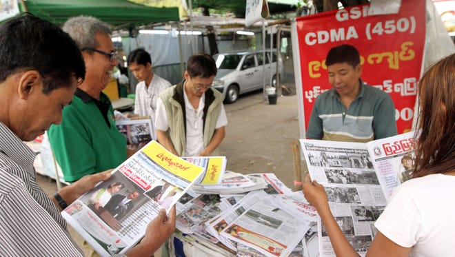 On Tuesday people browse local weekly news journals reporting U.S. President Barack Obama's trip to Myanmar at a newsstand, in Yangon, Myanmar.