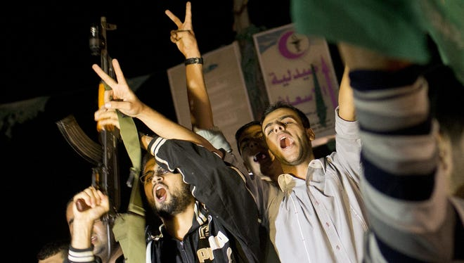 Palestinians celebrate the announcement of a cease-fire between Hamas and Israel in Gaza City, on Wednesday.