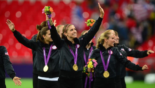 Alex Morgan (center) celebrates following the game against Japan during the London Olympic Games at Wembley Stadium on Aug. 9. U.S. national team players will play in a new league, U.S. Soccer announced.