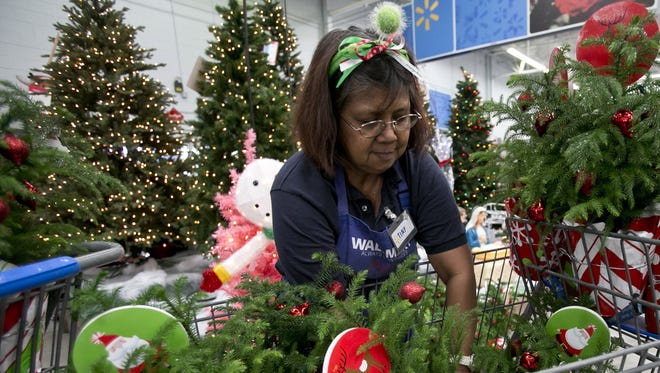 Walmart associate Tiny Applebee gets the holiday section ready ready for Black Friday shoppers.