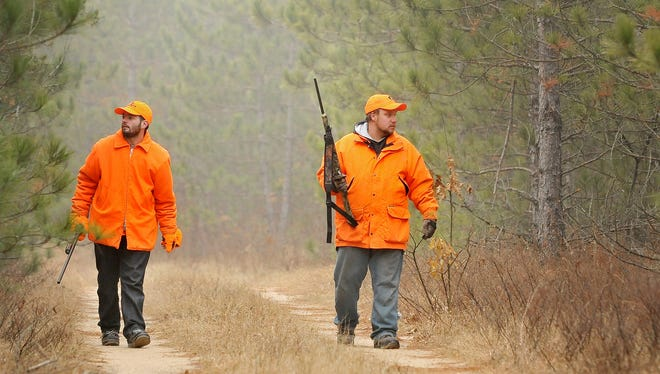 Donnie Kasat, left, and Mike Wagner of Eau Claire, Wis. walk along a trial in the Clark County forest near Fairchild, Wis. while hunting.