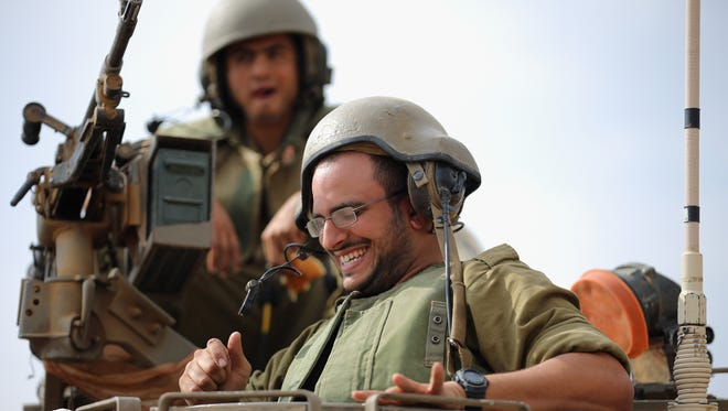 Israeli soldiers laugh and joke on their APC to music provided by visiting Hassidic Jews who visited to show their support to soldiers at the border with the Gaza Strip.