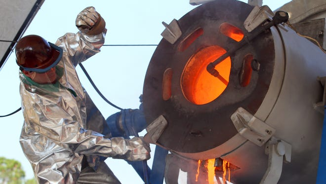 A worker in Gautier, Miss., pours molten metal into a mold on a job site.