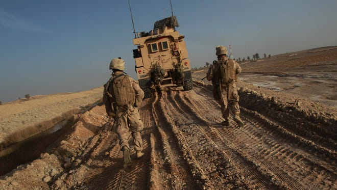 Marines walk on the tracks of a vehicle to avoid IEDs as their platoon tries to clear a route to reach another platoon in Afghanistan's Helmand province.