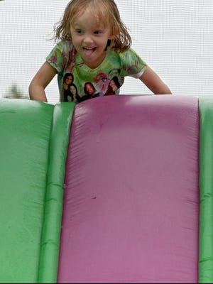 Riley Brown, 5, gets ready to the slide at the end of the inflatable bouncy course at a Labor Day picnic in Mansfield Park  in Muncie, Ind.