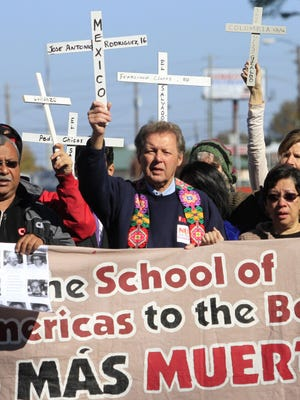 Former Roman Catholic priest Roy Bourgeois, center, leads protesters toward the gates of Fort Benning, Ga., during the annual School of the Americas Watch protest this past Sunday.