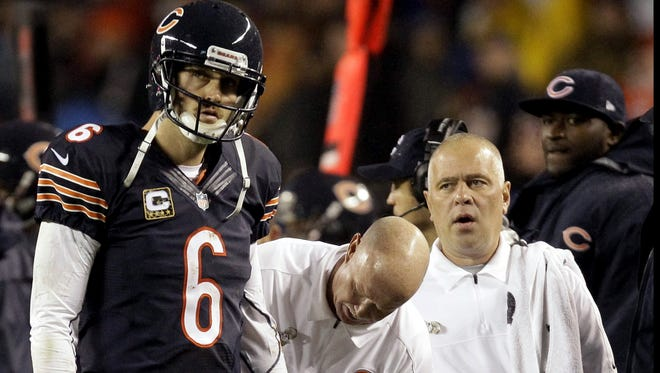 Trainers look at Chicago Bears quarterback Jay Cutler after Cutler took a late hit by Houston Texans linebacker Tim Dobbins in the first half of an NFL football game in Chicago on Nov. 11. The Texans won 13-6. Dobbins was called for an unnecessary roughness penalty on the play. Cutler did not return in the second half after suffering a concussion.