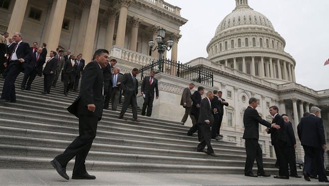 Newly elected freshmen of the 113th Congress walk away after having a group picture taken on Nov. 15.