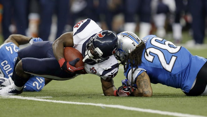 Houston Texans running back Justin Forsett is hit by Detroit Lions free safety Louis Delmas (26) during the third quarter of an NFL football game at Ford Field in Detroit, Thursday, Nov. 22, 2012. Forsett scored a controversial 81-yard touchdown on the play.