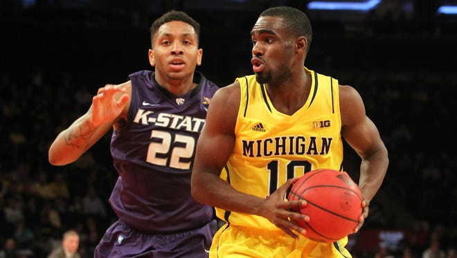 Michigan Wolverines guard Tim Hardaway Jr. (10) drives against Kansas State Wildcats guard Rodney McGruder (22) during the first half of the NIT Season Tip-Off championship game at Madison Square Garden.