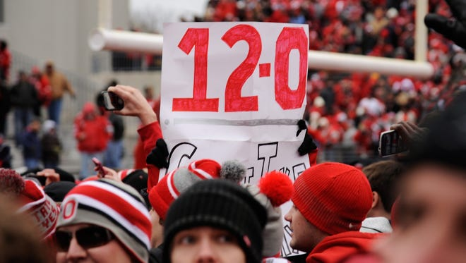 Ohio State Buckeyes fans storm the field and hold a sign showing Ohio State's season record after the Buckeyes defeated the Michigan Wolverines 26-21 at Ohio Stadium on Saturday.