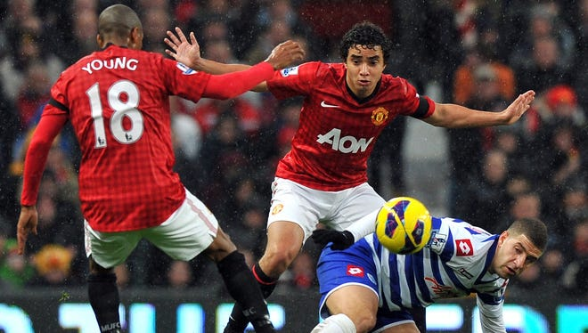 Manchester United's Rafael and Ashley Young challenge QPR's Adel Taarabt.