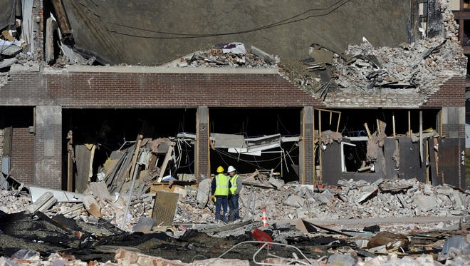 Inspectors stand in debris at the site of a gas explosion that leveled a strip club in Springfield, Mass., on Friday evening.