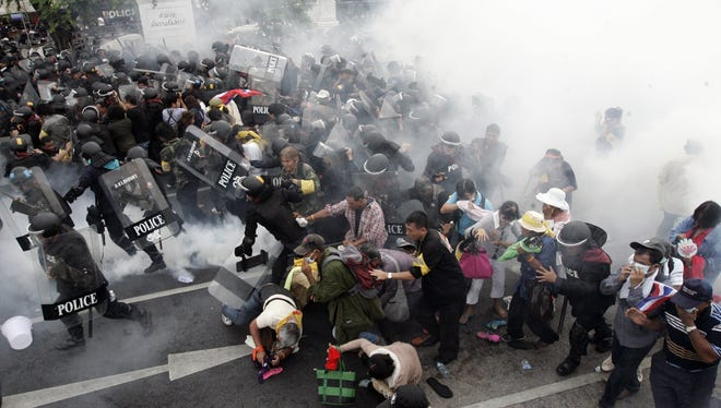 Anti-government protesters flee from tear gas fired by police in Bangkok, Thailand, on Saturday.