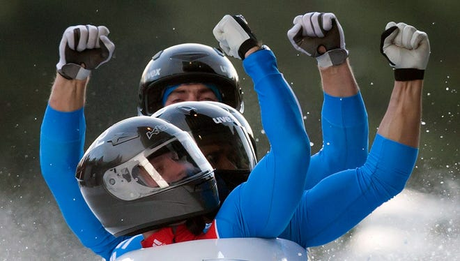 From front to back, Russia's Alexander Zubkov, Alexey Negodaylo, Dmitry Trunenkov and Maxim Mokrousov celebrate after winning four-man bobsled World Cup event.