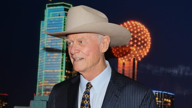 """American actor, director and producer, Larry Hagman, best known for his role as """"J.R. Ewing"""" from the TV series Dallas poses for a photo in front of a backdrop with an image of downtown Dallas, during a reception at the University of Texas at Tyler, following his presetation of """"Confessions"""" on Nov. 10, 2012.   Hagman, who for more than a decade played villainous patriarch JR Ewing in the TV soap Dallas, has died at the age of 81, his family said Saturday Nov. 24, 2012. (AP Photo/Dr. Scott M. Lieberman)"""