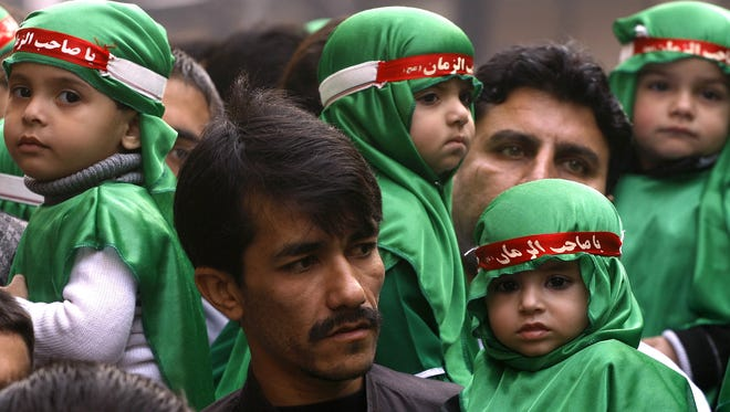 Pakistani Shiite Muslims carry children in a procession to mark Muharram in Peshawar, Pakistan on Friday.