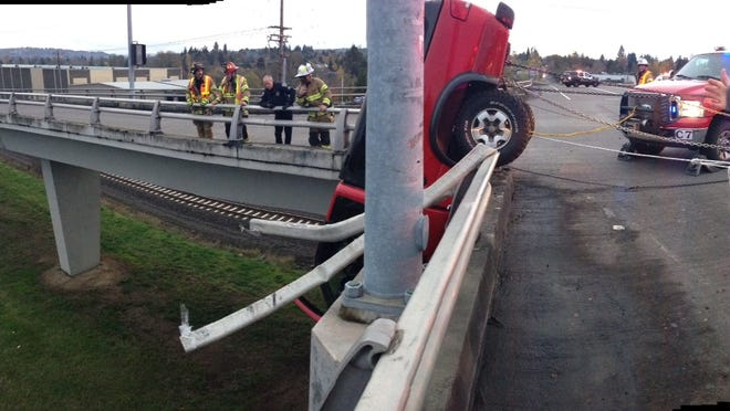 This image provided by the Beaverton Police Department shows a red pickup truck dangling from the Denney Road overpass near Highway 217 outside Beaverton, Ore.
