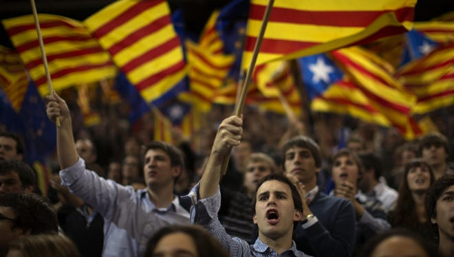 Supporters of center-right Catalan Nationalist Coalition leader Artur Mas wave their pro-independence flags during the last day of campaigning in Barcelona on Friday.
