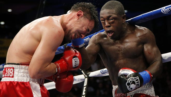 Robert Guerrero, left, takes a punch from Andre Berto in the 10th round of their WBC interim welterweight title fight Saturday in Ontario, Calif. Both fighters had eyes swellede shut during the fight, which was won by Guerrero.