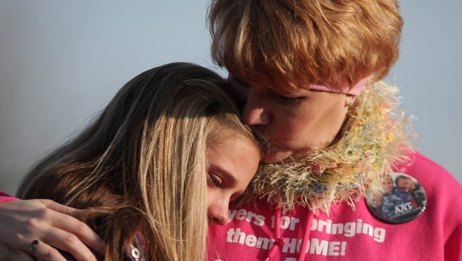 Tanya Zuvers, gives McKenna Shaffer, 12, a kiss, after she read a letter McKenna wrote to her missing cousins during a gathering Sunday, Nov. 25, 2012, at Wakefield Park in Morenci, Mich., to raise awareness and remember Zuvers' missing sons.