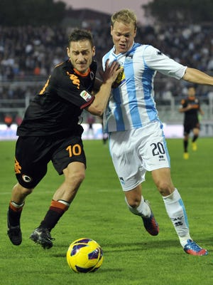 AS Roma forward Francesco Totti, left, and Pescara  Danish midfielder Matti Lund Nielsen vie for the ball during a Serie A soccer match between Pescara and AS Roma, at the Adriatico stadium in Pescara, Italy, Sunday, Nov. 25, 2012.