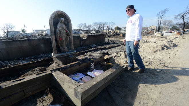 John Nies walks near his home at Breezy Point two weeks after Hurricane Sandy.
